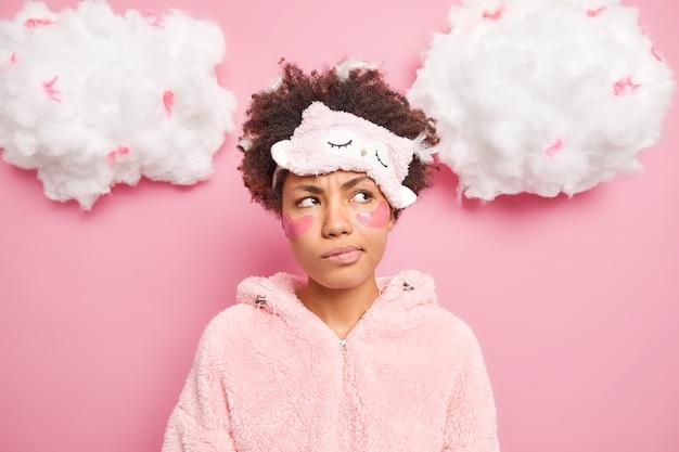 Retrato de mulher encaracolada pensativa e descontente olha pensativamente de lado, sorri afetado, rosto aplica manchas sob os olhos e usa pijama de dormir isolada sobre parede rosa