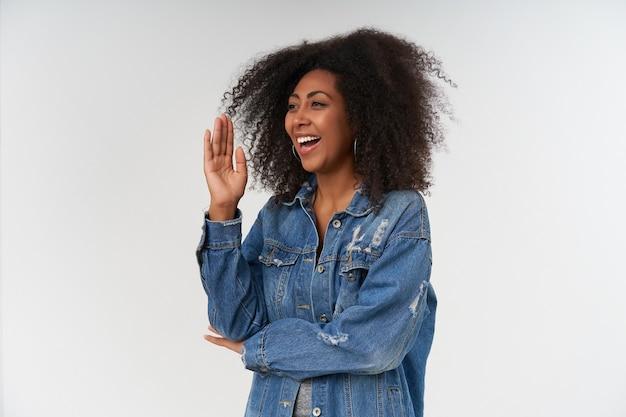 Retrato de mulher encaracolada positiva com pele escura, cruzando as mãos como uma aluna pronta para responder, olhando para o lado com um sorriso alegre enquanto posava sobre uma parede branca com roupas casuais