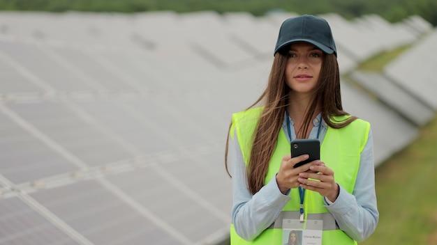 Retrato de mulher engenheira inspetor de uniforme usa smartphone na planta solar. trabalhador de fazenda solar em pé perto de fileiras com baterias. campo de painel solar. produção de energia limpa. energia verde.