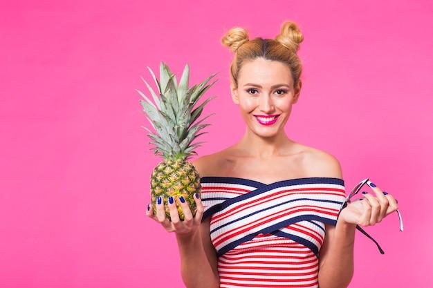 Retrato de mulher engraçada e abacaxi sobre fundo rosa. verão, dieta e conceito de estilo de vida saudável.
