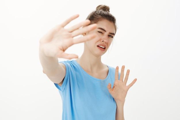 Retrato de mulher enojada e incomodada protegendo o rosto da luz, levantando as mãos na defensiva, gesto de parar