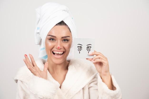 Retrato de mulher enrolada em uma toalha branca com paleta de sombras