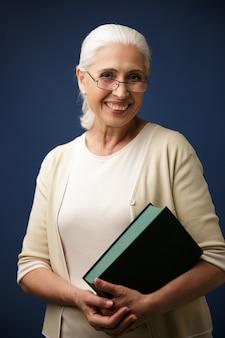 Retrato de mulher envelhecida alegre em copos, segurando o livro
