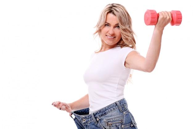Retrato de mulher envelhecida feliz com grandes jeans e halteres