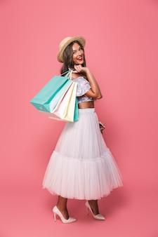 Retrato de mulher espantada comprador usando chapéu de palha e saia fofa segurando sacolas de papel colorido com compras