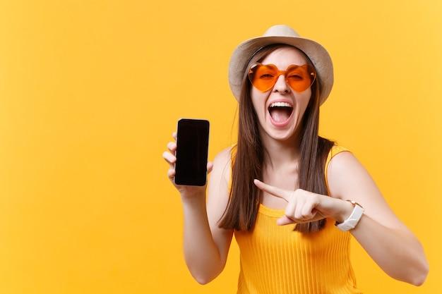 Retrato de mulher espantada e animada com chapéu de verão, óculos laranja mantém a boca aberta, parece surpreso, segure o telefone móvel com tela vazia em branco isolada em fundo amarelo. conceito de emoções de pessoas.