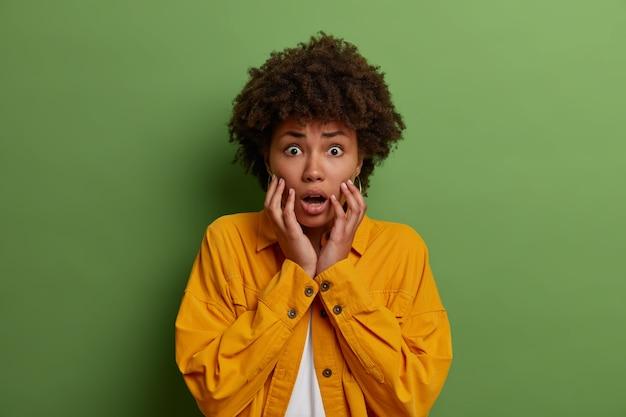 Retrato de mulher espantada e assustada agarra o rosto, fica alarmada como uma réplica de alguma coisa, ouve más notícias aterrorizantes, encara com olhos esbugalhados, vestida com jaqueta amarela, isolada no verde