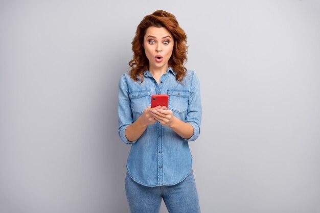 Retrato de mulher espantada usar smartphone ler rede social novidade impressionado gritar inacreditável inesperado usar roupa de boa aparência isolada sobre parede de cor cinza