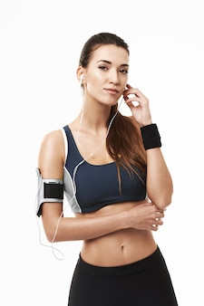 Retrato de mulher esportiva em fones de ouvido e sportswear posando em branco.