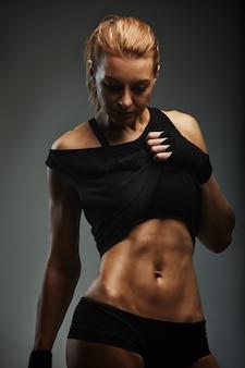 Retrato de mulher esportiva em roupas esportivas escuras em um fundo escuro