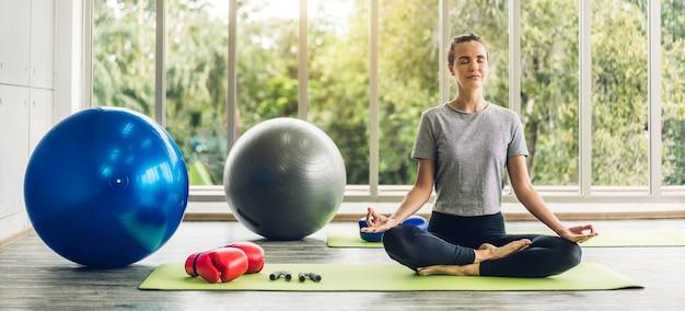 Retrato de mulher esportiva em roupas esportivas, sentada relaxando e praticando ioga fitness com fitball azul em casa