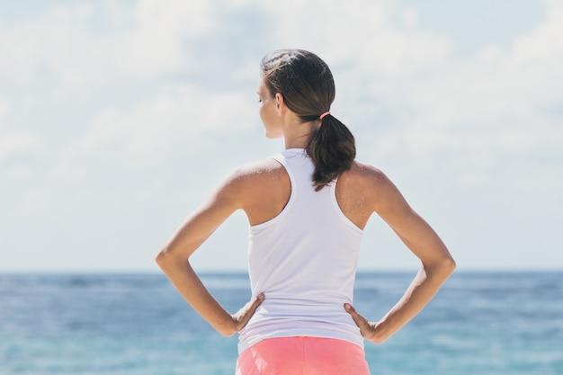 Retrato de mulher esportiva se aquecendo antes do treino com o mar