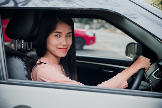 Retrato de mulher está sorrindo enquanto estiver dirigindo um carro.
