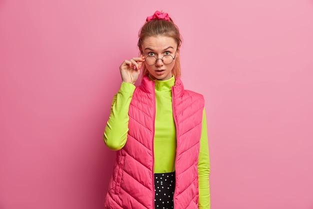 Retrato de mulher europeia adulta chocada olha através de óculos óticos, tem expressão de espanto, mantém a mão na borda dos óculos, surpresa com o que viu, usa roupas brilhantes