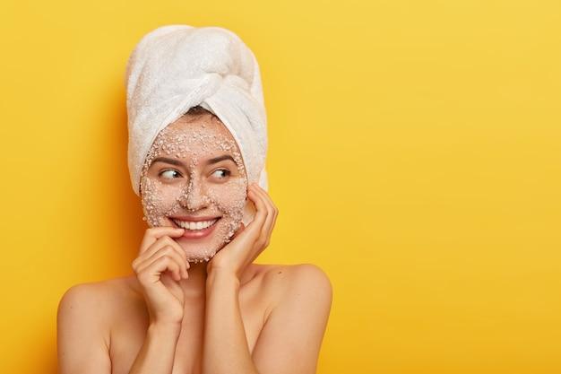 Retrato de mulher europeia aplica máscara facial orgânica para limpar a pele, cuida da tez, sorri gentilmente, mostra os dentes brancos, tem ombros nus, fica encostada na parede amarela com espaço em branco
