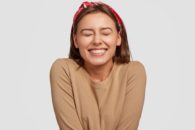 Retrato de mulher européia feliz com sorriso largo, fecha os olhos, sente empolgação, está em alta