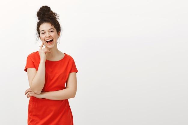 Retrato de mulher europeia feliz despreocupada em um vestido vermelho da moda com cabelos cacheados penteados em coque, rindo alto e tocando o rosto com a mão