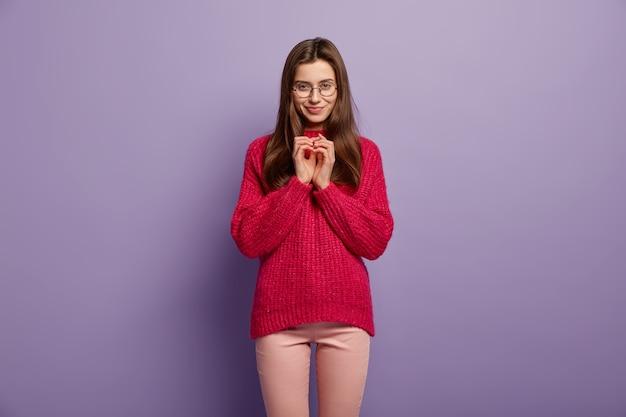 Retrato de mulher europeia satisfeita mantém as mãos juntas, tem intenção de fazer algo, usa blusão e calça vermelha, isolada sobre a parede roxa hmm, deixe-me pensar, tenho um bom plano
