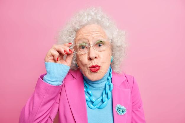 Retrato de mulher europeia sênior com cabelo encaracolado grisalho mantém a mão na borda dos óculos e mantém os lábios arredondados, vestida com roupas da moda