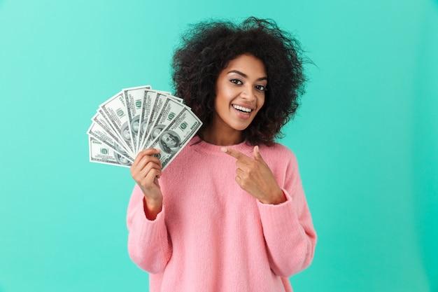 Retrato de mulher excitada 20 anos com penteado afro, apontando o dedo no ventilador de notas de dólar de dinheiro, isolado sobre a parede azul