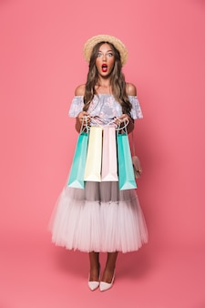 Retrato de mulher excitada com chapéu de palha e saia fofa segurando pacotes de compras de papel colorido