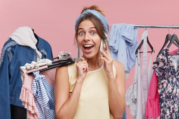 Retrato de mulher excitada falando por telefone inteligente, segurando os cabides com roupas na mão, olhando com felicidade e surpresa