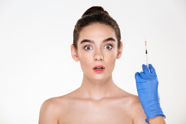 Retrato de mulher excitada ou assustada, preparando-se para injeções de ácido hialurônico no rosto, tendo tratamento com cuidados com a pele na clínica