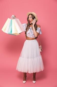 Retrato de mulher excitada usando chapéu de palha e saia fofa segurando sacolas de papel colorido e falando no celular