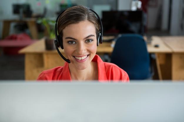 Retrato de mulher executiva com fones de ouvido no escritório criativo
