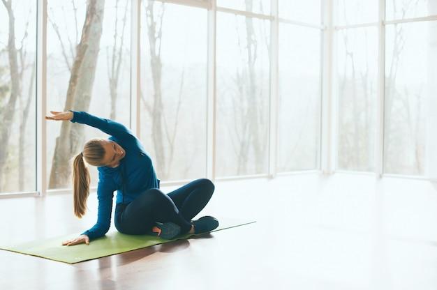 Retrato de mulher fazendo alongamento no estúdio durante o período da manhã