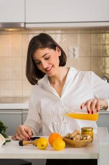Retrato de mulher fazendo suco de laranja fresco