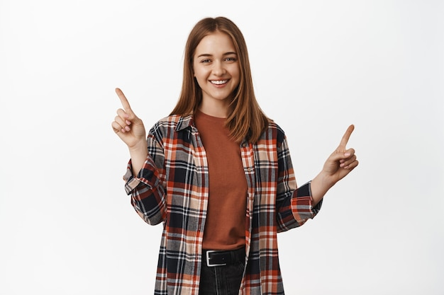 Retrato de mulher feliz apontando para a venda, mostrando descontos de lado, duas opções, variantes de itens com descontos, sorrindo na frente, parede branca