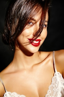 Retrato de mulher feliz bonita morena sexy bonita com lábios vermelhos em lingerie de pijama em fundo preto