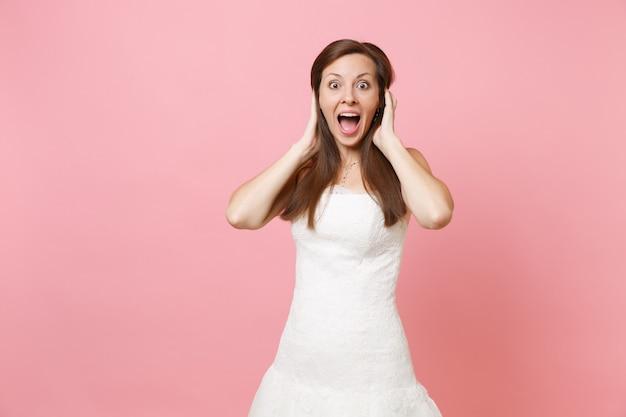Retrato de mulher feliz chocada e animada em um lindo vestido branco em pé agarrado à cabeça