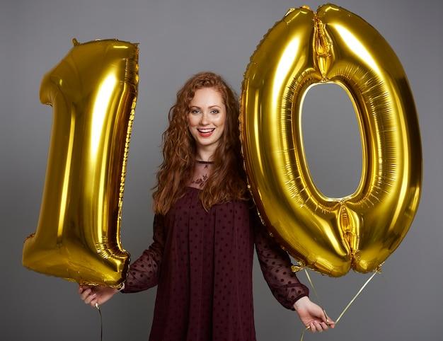 Retrato de mulher feliz com balões em formato de dez