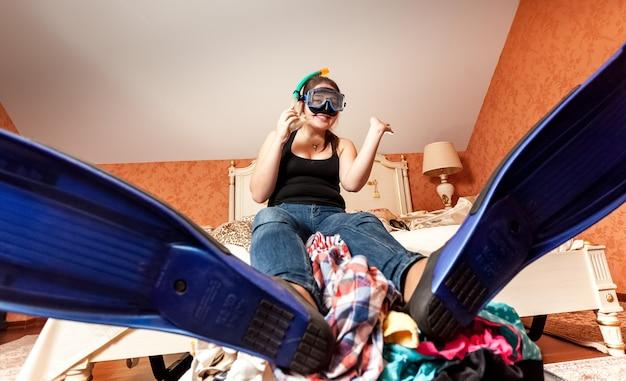 Retrato de mulher feliz com nadadeiras e máscara sentada na mala em casa