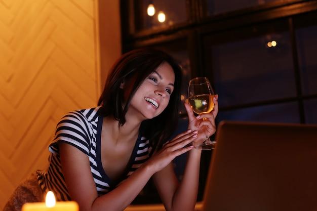 Retrato de mulher feliz com um copo de vinho, olhando para a tela do pc