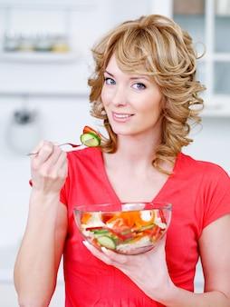 Retrato de mulher feliz comendo salada de legumes na cozinha