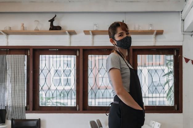 Retrato de mulher feliz dona de café e restaurante com máscara facial