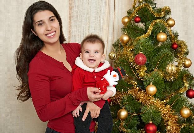 Retrato de mulher feliz e bebê na decoração de natal