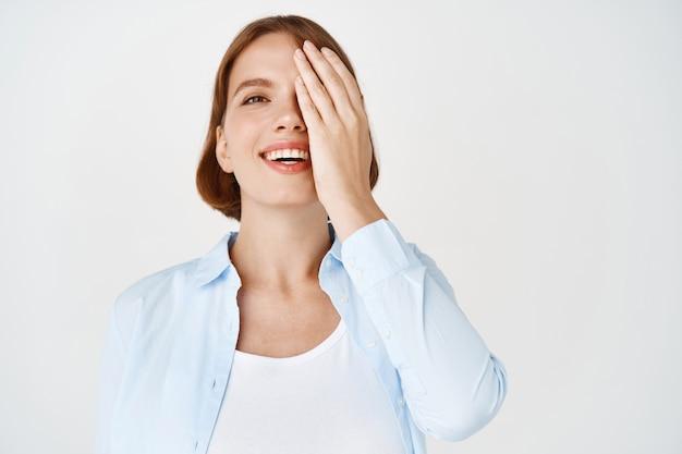 Retrato de mulher feliz e natural cobrindo metade do rosto e sorriso, de blusa contra a parede branca