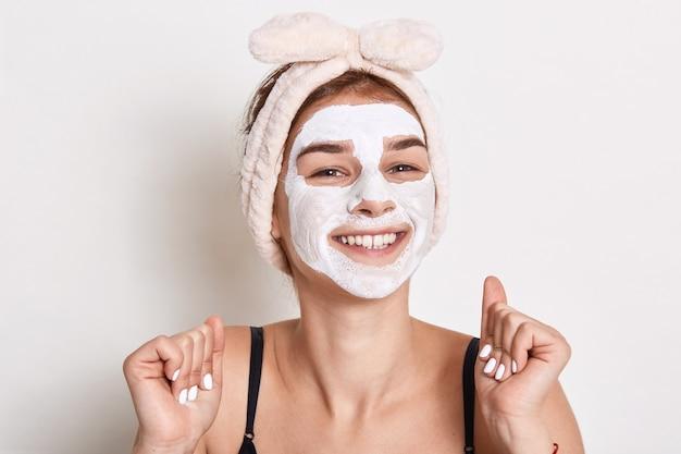 Retrato de mulher feliz e satisfeita com máscara facial de beleza, sorri deliciosamente, tem aparência agradável, senhora fazendo procedimentos de cuidados com a pele.