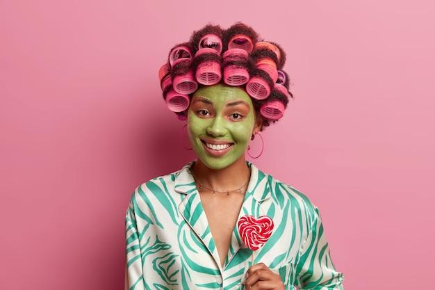 Retrato de mulher feliz étnica usa máscara facial verde, sorri com os dentes, segura pirulito, faz penteado encaracolado com rolos, usa roupas domésticas casuais.
