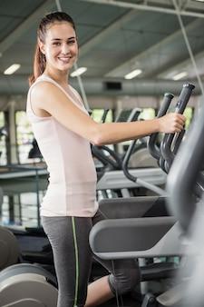 Retrato de mulher feliz exercitando na máquina elíptica