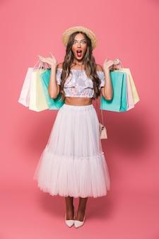 Retrato de mulher feliz glamour usando chapéu de palha e saia fofa segurando sacolas de papel colorido