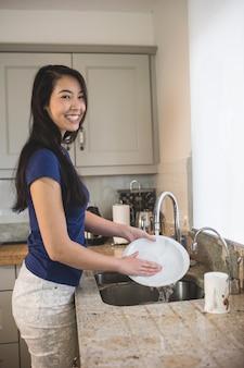 Retrato de mulher feliz lavando na cozinha