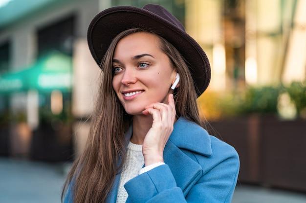 Retrato de mulher feliz na moda elegante hipster de chapéu com fones de ouvido brancos sem fio ouve música no centro da cidade. pessoas e tecnologia modernas