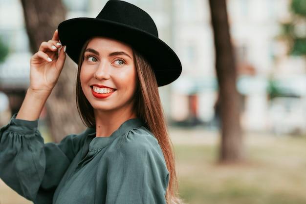 Retrato de mulher feliz posando com um chapéu preto