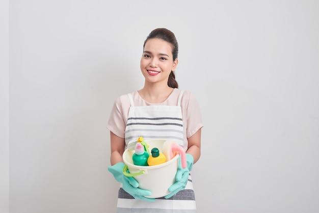 Retrato de mulher feliz, segurando nas mãos produtos de limpeza em casa e começando a limpar.