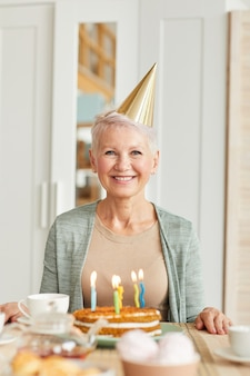 Retrato de mulher feliz sênior com chapéu, sentado à mesa com bolo de aniversário e sorrindo para a câmera em casa